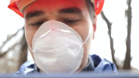 r Ένα άτομο σε ένα κράνος και μια αναπνευστική συσκευή με μια ταμπλέτα μετρά το επίπεδο ρύπανσης του νερού αποβλήτων απόθεμα βίντεο