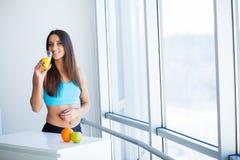 r Ευτυχής χαμογελώντας νέα γυναίκα που πίνει το χυμό από πορτοκάλι στοκ εικόνες