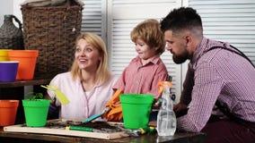 r r Καλλιεργώντας οικογένεια Γονέας κήπων Το αγόρι παιδιών βοηθά τους γονείς του για να φυτεψει και να φροντίσει λουλούδια Φιλί α απόθεμα βίντεο