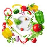 r Λαχανικά που πετούν σε μια περιστροφή για μια σαλάτα πέρα από ένα πιάτο στοκ φωτογραφίες