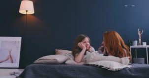 r Μητέρα και το κορίτσι παιδιών κορών της που παίζουν και που αγκαλιάζουν στο κρεβάτι στην κρεβατοκάμαρα απόθεμα βίντεο