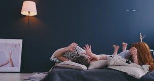 r Μητέρα και το κορίτσι παιδιών κορών της που παίζουν και που αγκαλιάζουν στο κρεβάτι στην κρεβατοκάμαρα φιλμ μικρού μήκους