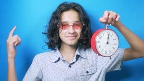 r ο αστείος έφηβος στα ρόδινα γυαλιά κρατά ένα ρολόι στα χέρια της και παρουσιάζει στα δάχτυλά της σημάδι χρημάτων απόθεμα βίντεο