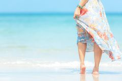 r Ο τρόπος ζωής που χαμογελά την ασιατική γυναίκα που φορά τα θερινά ταξίδια μόδας φορεμάτων χαλαρώνει στην αμμώδη ωκεάνια παραλί στοκ φωτογραφία