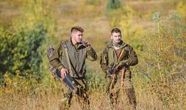 r Παράνομο κυνήγι Οι φίλοι κυνηγών απολαμβάνουν τον ελεύθερο χρόνο Κυνηγοί με τα τουφέκια μέσα στοκ εικόνες