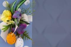 r Συγχαρητήριο υπόβαθρο Πάσχας Αυγά Πάσχας και λουλούδια στοκ εικόνες