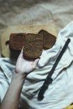 r Τέμνον ψωμί χεριών Τεμαχισμός ενός ψωμιού r στοκ εικόνα