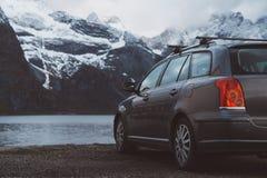 r Автомобиль на предпосылке снег-покрытых гор и озер Всход от задней части Смогите использовать как знамя стоковые фото