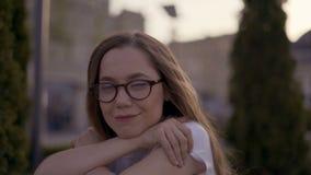 r девушка со стеклами сидит на траве в парке 4K акции видеоматериалы