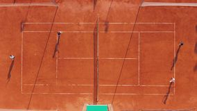 r Игроки играют теннис на оранжевом суде сток-видео