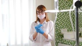 r Медсестра больницы моет ее руки в стерильных перчатках перед медицинскими процедурами Женский получать доктора сток-видео