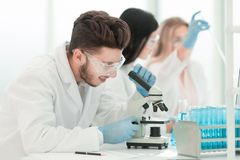 r мужской ученый использует микроскоп в лаборатории стоковое изображение