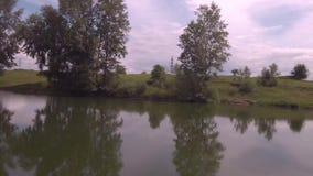 r Низкий полет над озером на солнечном утре лета Зеленые деревья и холмы, отражение облаков на озере сток-видео