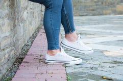 r Ноги маленькой девочки в голубых брюках джинсовой ткани и белых тапках стоковое фото