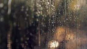 r Стекло Misted Жидкостные дождевые капли на окне Defocused автоматические светофоры на дне захода солнца Тоскливость a сток-видео
