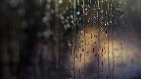 r Стекло Misted Жидкостные дождевые капли на окне Defocused автоматические светофоры на дне захода солнца Тоскливость a акции видеоматериалы