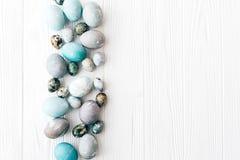r Стильная квартира границы пасхальных яя кладет на белую деревянную предпосылку с космосом для текста самомоднейше стоковые изображения rf