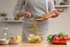 r Шеф-повар льет авокадо, в процессе вегетарианского салата в домашней кухне : Меню ресторана, меню стоковое изображение rf