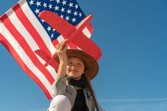 r 一个牛仔帽的美女在美国国旗的背景拿着一架红色飞机 美国庆祝第4 库存图片