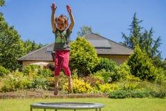 r 一点非常愉快的逗人喜爱的儿童女孩喜欢跳在绷床 r 免版税库存图片