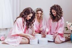 r 三个女孩庆祝一个单身聚会或生日,给在桃红色丝绸晨衣的礼物 免版税库存图片