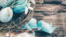 r 五颜六色的蓝色鸡蛋和春天snowdrop花在木背景 复活节假日贺卡 库存照片