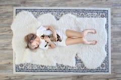 r 亚裔妇女使用与猫在客厅 在说谎在羊毛地毯的妇女的容忍的猫 免版税库存图片