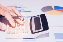 r 企业或帐户运转的计算器的手,赢利或者图表经济在家庭办公室 库存照片