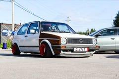r 俄罗斯- 2019年5月20日:在姿态样式大众高尔夫球调整的白色mk 1 有在街道上停放的宽红色轮子的低汽车 免版税库存图片