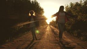 r 儿童旅客 青少年的女孩旅行并且握手 有沿国家跑的背包的愉快的女孩旅客 股票录像