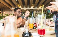 r 咖啡馆的吃寿司卷,饮用的饮料的多文化公司年轻人公司获得乐趣 库存图片