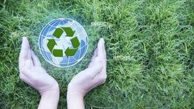 r 回收的女性手藏品地球和标志在绿草背景 生态和环境保护 地球da 免版税库存照片