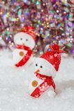 r 在他们的雪人红色帽子和围巾 在白雪的雪人在五颜六色的光亮的bokeh背景旁边 免版税库存照片