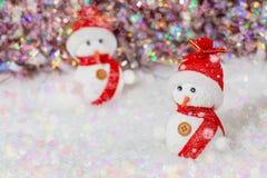 r 在他们的雪人红色帽子和围巾 在白雪的雪人在五颜六色的光亮的bokeh背景旁边 库存图片