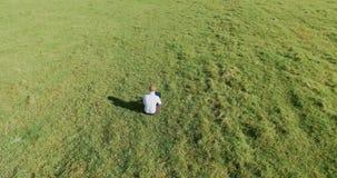 r 在商人的低轨道飞行坐与笔记本垫的绿草在领域 影视素材