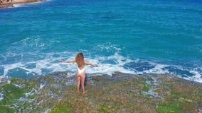 r 在峭壁的性感女孩身分在多岩石的海滩 妇女调查距离 股票视频