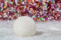 r 在闪烁的bokeh雪和美好的被弄脏的五颜六色的背景的白色球珍珠层珍珠与发光的光的 免版税库存照片