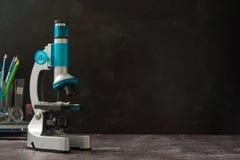 r 在黑背景隔绝的显微镜 学习在学校实验室的生物 库存照片