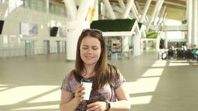 r 坐在机场休息室和饮用的咖啡的可爱的妇女 股票录像