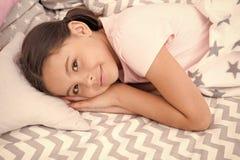 r 女孩微笑的愉快的孩子在与特征模式枕头和逗人喜爱的格子花呢披肩的床放置在她的卧室 ?? 免版税库存图片