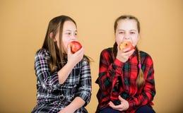 r 女朋友吃苹果快餐,当放松时 学校快餐概念 青少年与 免版税库存图片