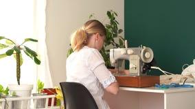 r 年轻白肤金发的妇女在一台打字机缝合在一间明亮的屋子 股票视频