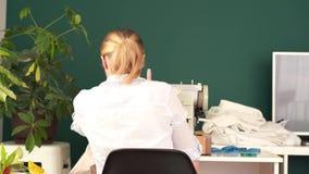r 年轻白肤金发的妇女在一台打字机缝合在一间明亮的屋子 股票录像