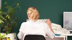 r 年轻白肤金发的妇女在一台打字机缝合在一间明亮的屋子 影视素材