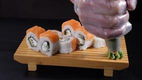 r 慢动作食物概念 专业厨师特写镜头  在木板材的倾吐的山葵有寿司卷的 股票视频
