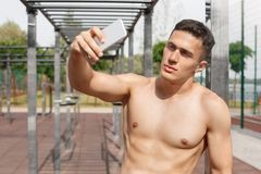 r 户外采取在智能手机的年轻人赤裸上身的身分selfie看确信的照相机 免版税库存图片