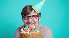 r 拿着生日蛋糕的党帽子的微笑的愉快的疯狂的年轻人 影视素材