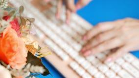 r 时髦的招呼的显示卡 女性手在一个桃红色键盘键入,在花旁边 在蓝色 股票录像