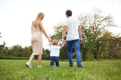 r 有孩子的家庭在公园走 库存照片
