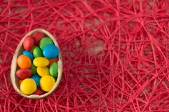 r 朱古力蛋用多彩多姿的糖果在桃红色背景说谎 免版税库存照片